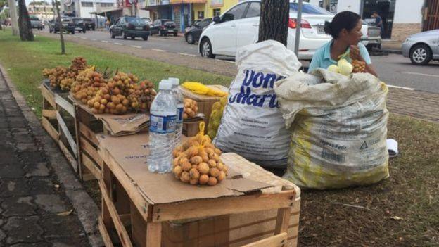 Mulher vende frutas no farol