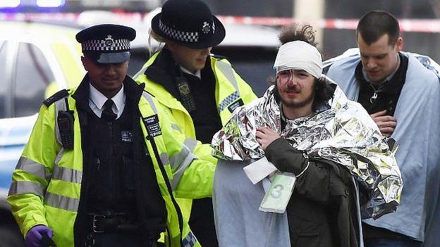 Des hommes blessés soutenus par la police