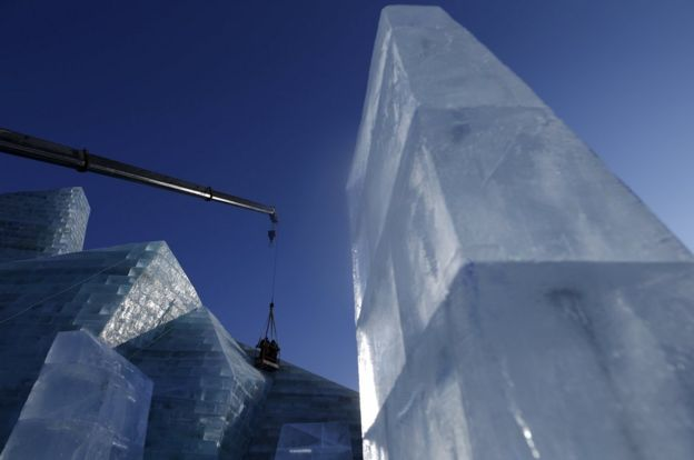 Workers polish an ice sculpture