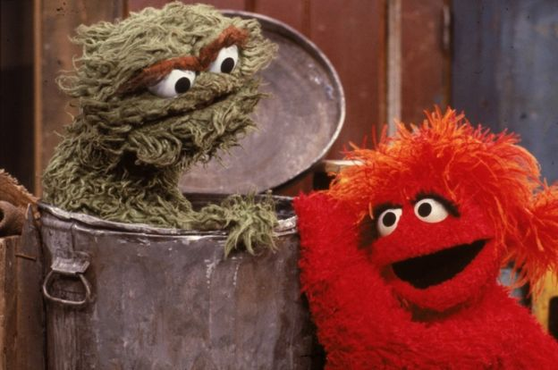 A red muppet visits Oscar the Grouch, inside his garbage can, in a scene from