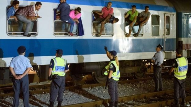 Police officers look at migrants sitting on the windows of a train at the railway station, near the Slovenian-Croatian border in Dobova, Brezice, on September 17, 2015.