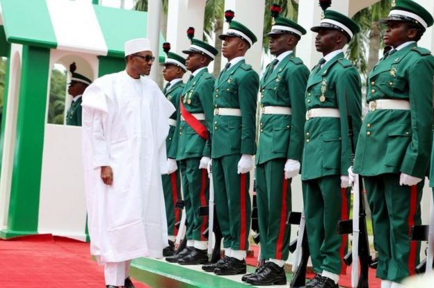 Nigerian president Muhammadu Buhari (L) inspects guards of honour as part of Nigeria's independence anniversary celebrations on 1 October 2015 in Abuja