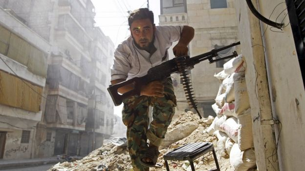 A rebel fighter takes cover during clashes with the Syrian army in the Salahuddin district of Aleppo (7 August 2012)