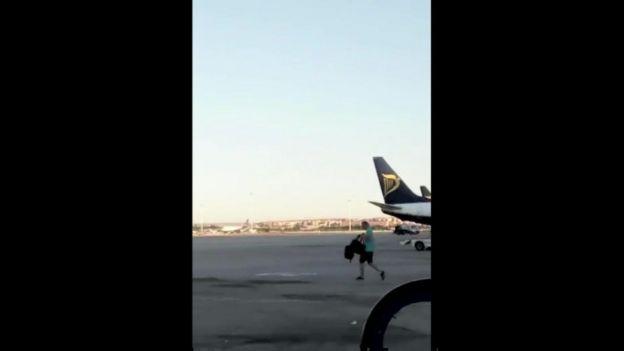 Man walking past plane tail
