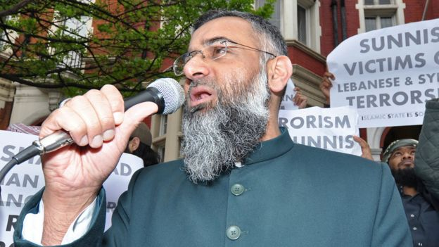 Poster behind Choudary includes small print words