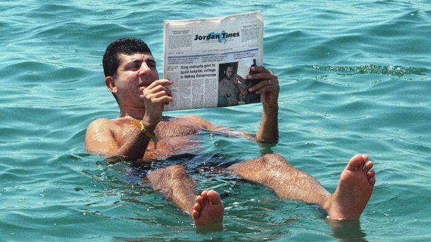 Un hombre lee el periódico mientras flota en el Mar Muerto el 31 de agosto de 1999
