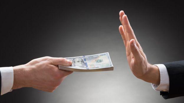 Homem rejeitando oferta de dinheiro