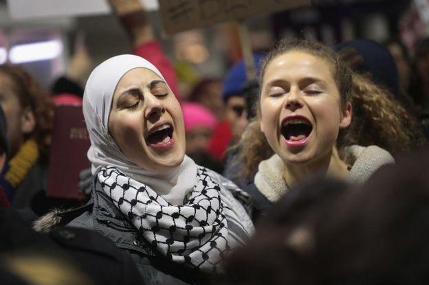 Dos mujeres protestan contra la orden ejecutiva del presidente de EE.UU., Donald Trump, en el aeropueto de Chicago.