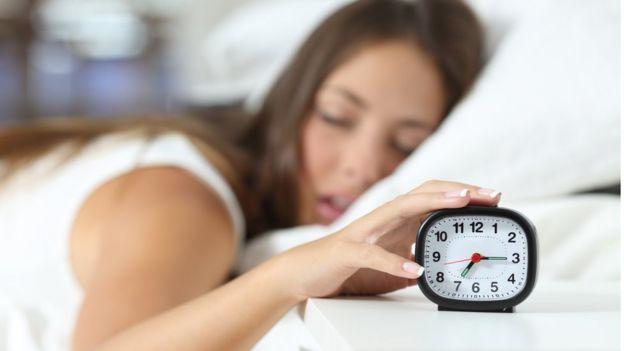 Mujer con un despertador.