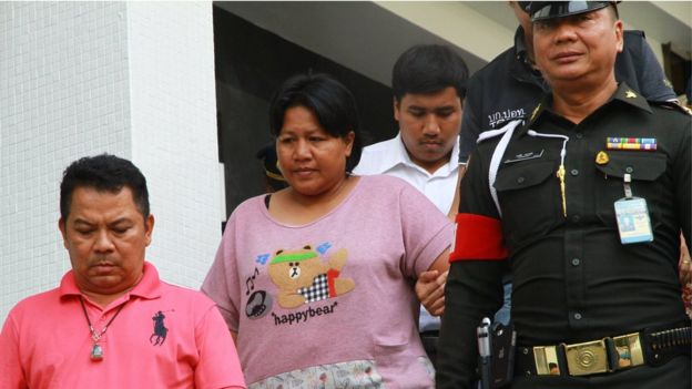 Ms Patnaree Chankij, wearing a pink T-shirt reading 'happybear' being escorted by police down a staircase, as she leaves a military court in Bangkok on 8 May 2016