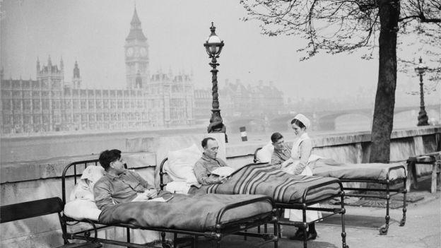 Pacientes en camas al lado del río y enfermera.