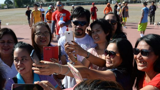 Philippine boxing icon Manny Pacquiao (C) poses for photos with visitors in General Santos City, in southern island of Mindanao on February 19, 2016