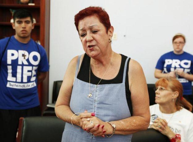 Norma McCorvey en una reunión con jóvenes con camisetas con las inscripciones