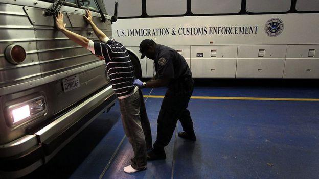 Agente de ICE revisando a un inmigrante indocumentado.