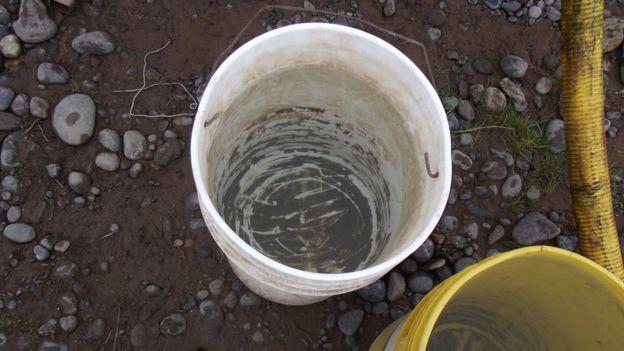 Cubo con agua y un residuo oscuro en el fondo.