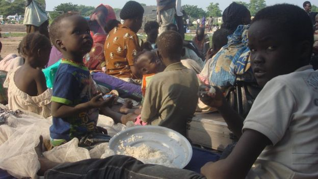 two children, one about 5 and the other about 12 years old, eating from a plate of rice while sitting on blankets surrounded by other people, 11 July