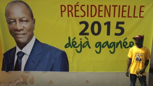 A supporter of Guinea's incumbent president and presidential candidate Alpha Conde stands in front of his campaign banner