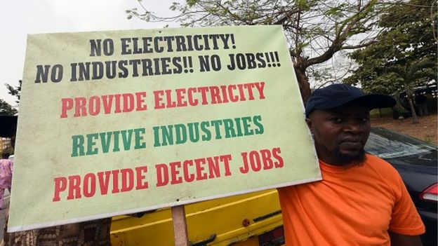 A man holds a placard reading 'No electricity! No industries!! No jobs!!! Provide electricity, revive industries, provide decent jobs' during a demonstration to protest against the 45 percent raise of electricity prices on February 8, 2016 in Lagos