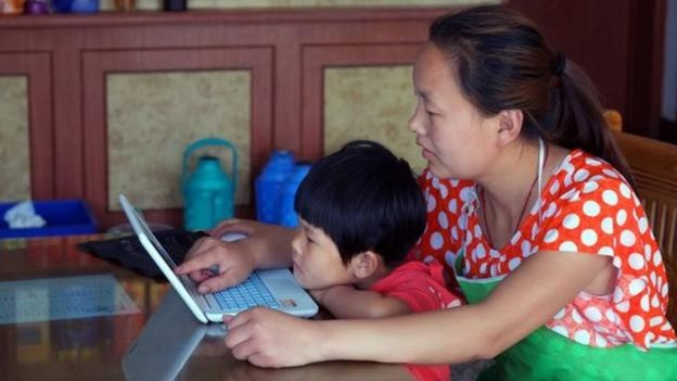Una madre china y su hijo usando una laptop