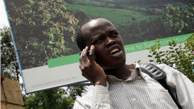 A man talks on a mobile phone while standing next to a huge Safaricom bill board after the launch of the Initial Public Offer (IPO) shares in Nairobi 28 March 2008.