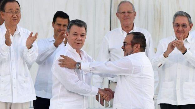 Rais wa Colombia Santos, kushoto na kiongozi wa waasi ajulikanaye kama Timochenko wamepeana mikono baada ya kutia saini mkataba huo