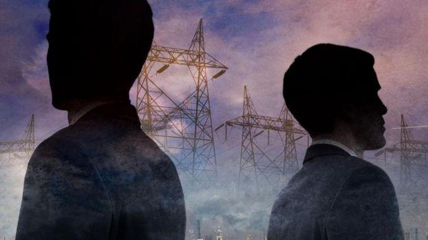 El perfil oscurecido de dos hombres de espaldas. Al fondo, unas torres de electricidad