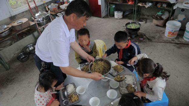 """Un maestro en una escuela rural de China da de comer a sus únicos cinco alumnos. La situación en muchas aldeas es """"desoladora"""", según Yuwen Wu."""