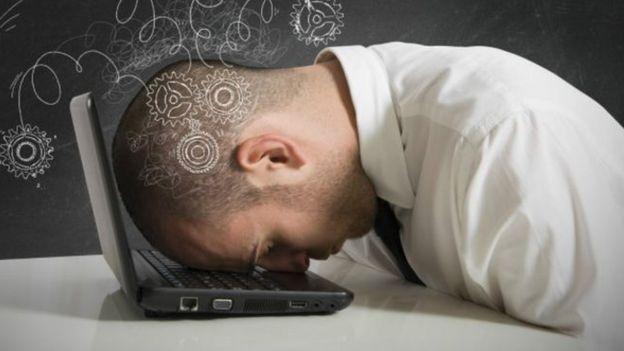 Hombre durmiendo sobre el teclado del computador.