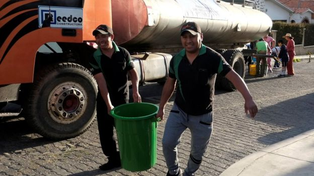 Dos personas cargan una gran cubeta de agua.