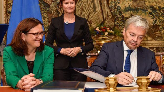 El canciller belga, Didier Reynders firma el acuerdo belga sobre Ceta en presencia de la comisario europea de Comercio, Cecilia Malmstrom.