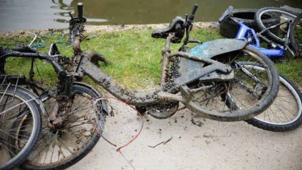 A Barclays bicycle on the canal bank as volunteers and staff from the Canal River Trust remove rubbish and some more bizarre objects that have been dumped into an East London Canal