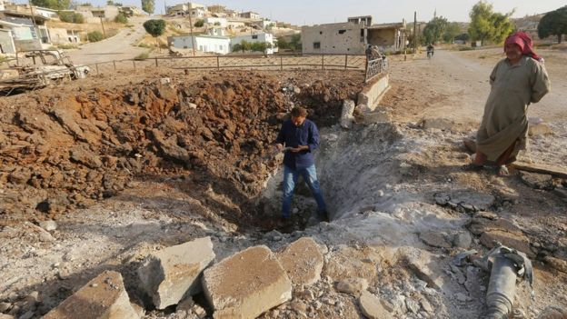A Syrian man stands inside a crater caused by what activists said was a Russian air strike in Latamneh, Hama province (2 October 2015)