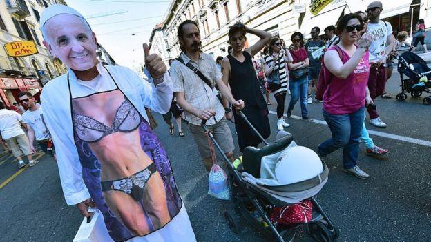 Protesta callejera a favor del matrimonio igualitario, con una imagen de un cuerpo en bikini con una máscara del papa Francisco en la cara.