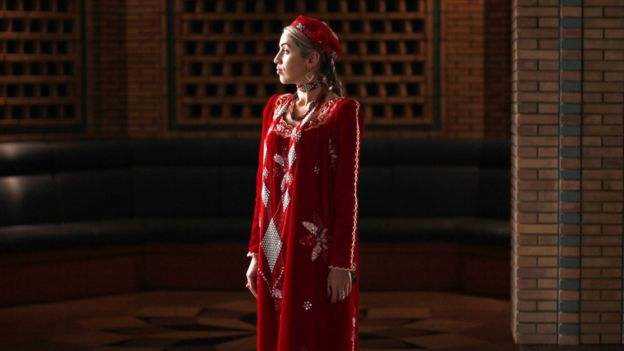 A woman in traditional dress waits on October 22, 2011 for the departure of US Secretary of State Hillary Clinton, who spoke at a town hall discussion at the Ismaeli Center in Dushanbe