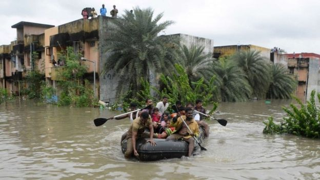 Indian rescue personnel and police officials paddle an inflatable boat through floodwaters as they evacuate residents in Chennai on December 2, 2015