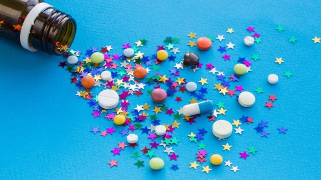 Un frasco con pastillas y estrellas de colores