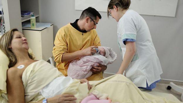 Un hombre da un biberón a un bebé recién nacido junto a la cama donde se encuentra la madre.
