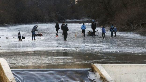 Los jóvenes juegan en una sección cubierta de hielo del río Esca en Burgui, provincia de Navarra, España, el nueve de enero de 2017.