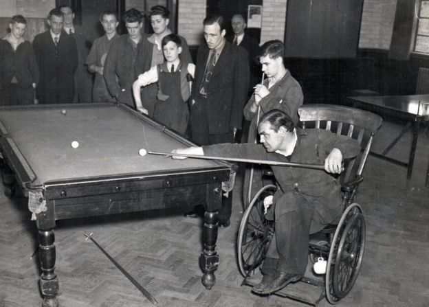 A wheelchair user playing pool 1940s