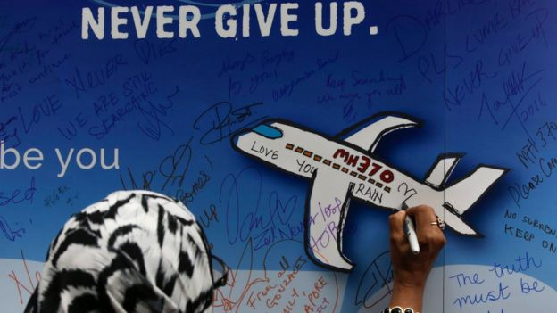 A file picture dated 06 March 2016 shows a woman writing messages for the passengers of missing Malaysia Airlines flight MH370 on a banner during a remembrance ceremony to mark the second anniversary of the plane