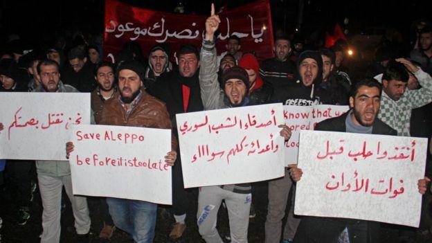 Residentes sirios del lado oeste de Alepo protestan con carteles.