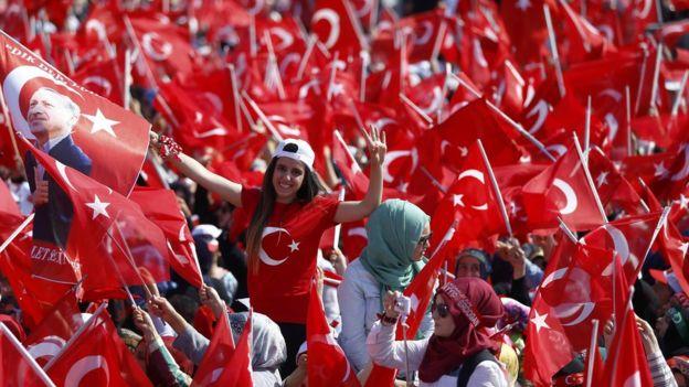 Kalabalık arasında genç bir kız elinde Türk bayrağı taşıyor.