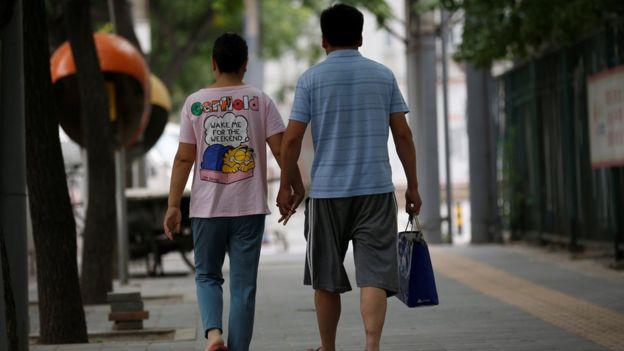 Dos ciudadanos chinos de espaldas. Caminan de la mano.