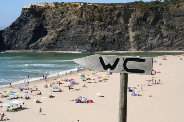 WC sign pointing to the sea