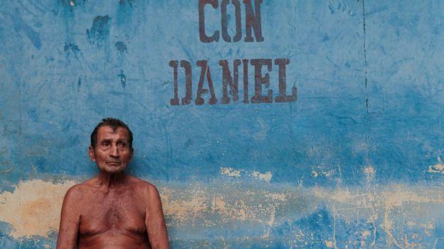Un hombre sin camisa frente a una pared donde se lee
