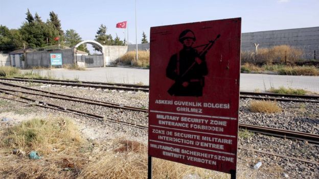 A Turkish military warning sign, with the closed Karkamis border gate in the background