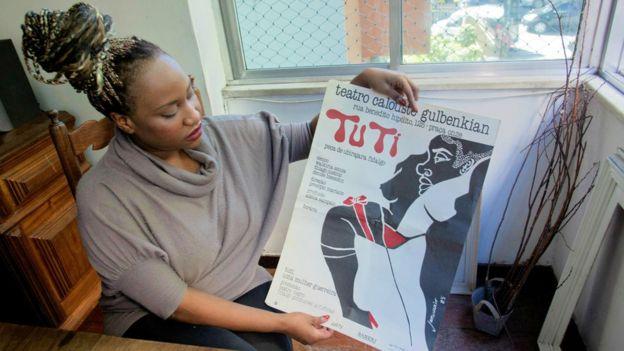 A cineasta Sabrina Fidalgo com cartaz da companhia de teatro fundada por seu pai