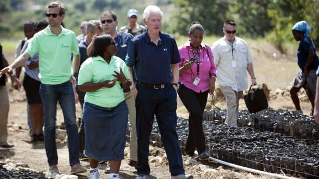 Bill Clinton (C) tours a Clinton Foundation project in Mirebalais, in the central plateau of Haiti, on 23 February 2015