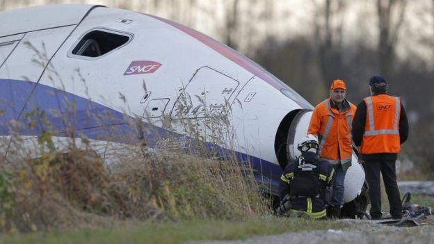 Workers at the wreckage of a derailed TGV train in France