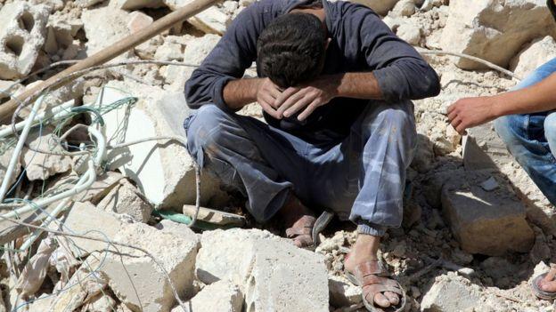 Homem reage à morte de familiares após um ataque aéreo das forças de Assad em Alepo